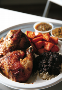 Chicken with sides of sweet potatoes and black beans with rice